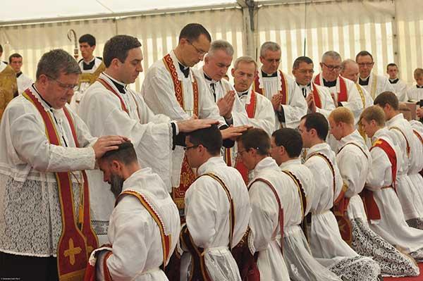 i sacerdoti impongono le mani agli ordinandi sacerdoti